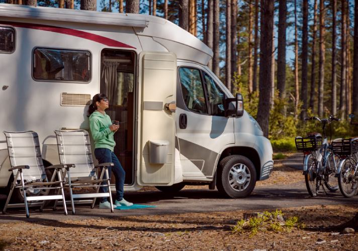 Another person standing next to an RV with coffee in hand. There are bicycles in the background.