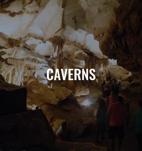 Cavern with people walking inside. There is a text overlay that reads Caverns.