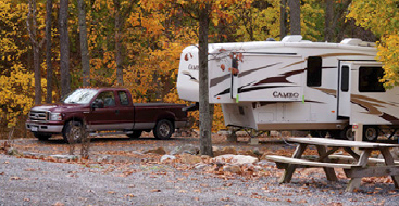 Truck attached to a camper. There is a picnic table in the foreground and the background trees are colored green to orange.
