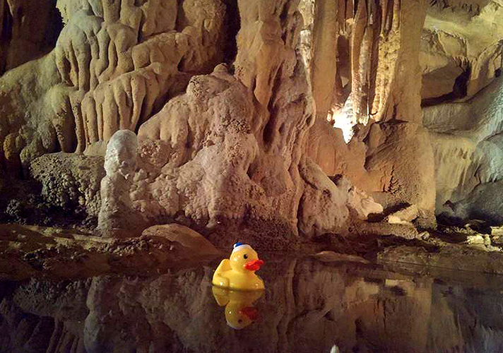 Puddle of water on bottom of cave floor with yellow rubber duck floating.