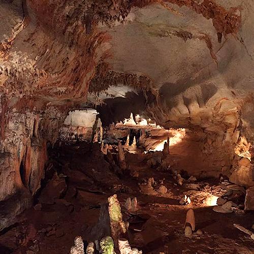Interior of a deep cavern with lights illuminating it.