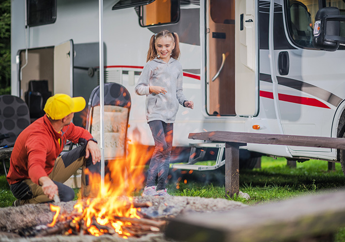 A father creating a campfire in front of an RV with his daughter.