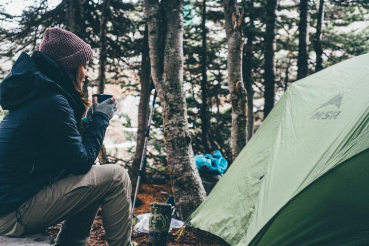Woman wearing warm clothes drinking from a mug outside a tent.
