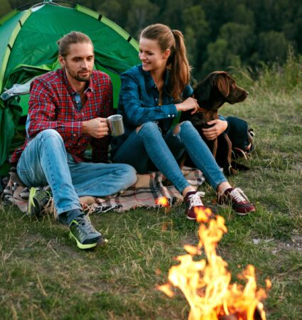 Man And Woman Traveling With Dog At Camp. Happy Couple Travel With Dog In Nature. Smiling Young People Sitting Near Camping Tent And Playing With Pet, Traveling On Weekend. High Quality Image