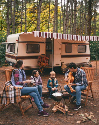 Happy family on a camping trip relaxing in the autumn forest. Camper trailer. Fall season outdoors trip.